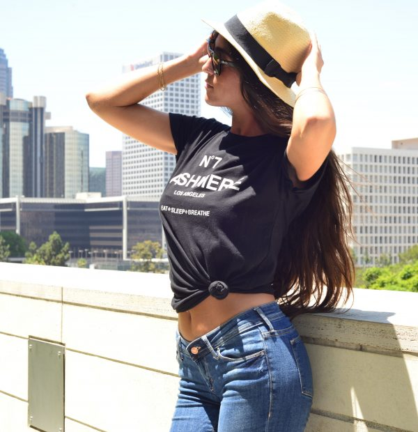 Our model wearing the Black No 7 Cashmere inspired T-Shirt with a city backdrop