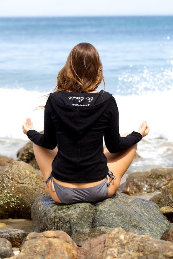 Cashmere Hoodie Nicki Jacket in black worn by our model at the beach facing her back towards camera